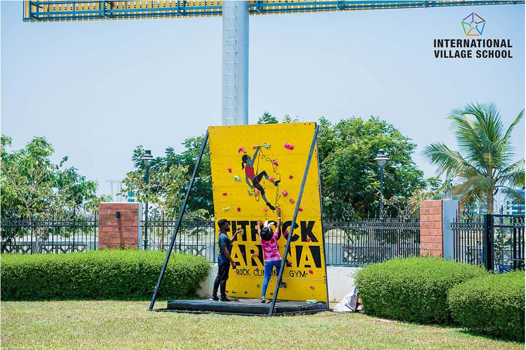 A Big yellow colour board advertising FIT Rock Arena -Rock climbing Gym  with a man guiding the student to climb organized by International Village School in Chennai as part of  After School Program