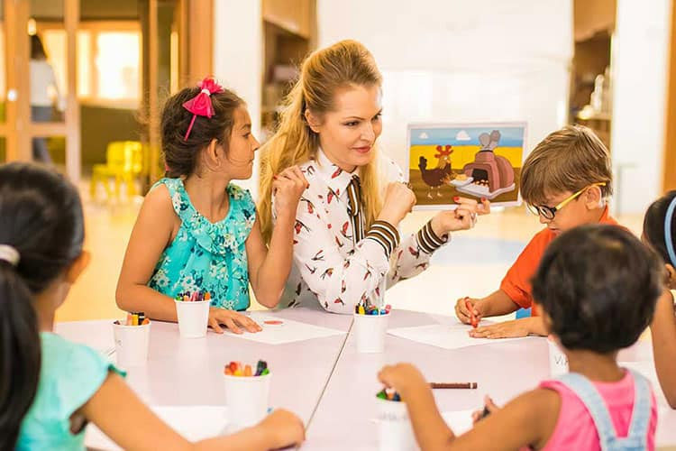 Teacher with painting in her hand  guiding the small students by making them sit around the white table inside the classroom