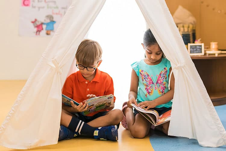 Two kids reading books inside the cloth tent  inside our school library