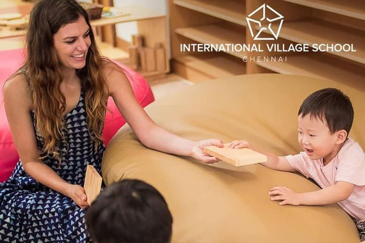 Teacher holding two small wooden blocks and giving one to small kids and he is happily getting it from her