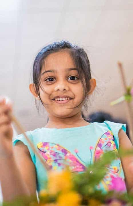 A girl in a light blue colour dress participating in environmental initiatives drive at her school  International Village School, the  best IB board school in Chennai