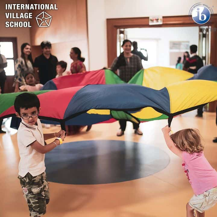 Few small students of our IB School holding the big colourful cloth exhibiting the fun in the hall and few parents are discussing with teachers beside them